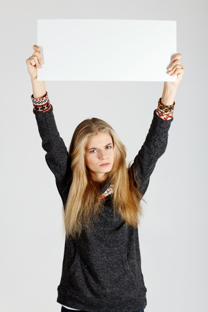 Young woman holding blank placard  Studio shot photo