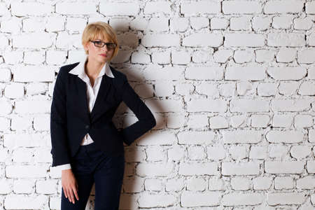brick background: Beautiful blonde young businesswoman
