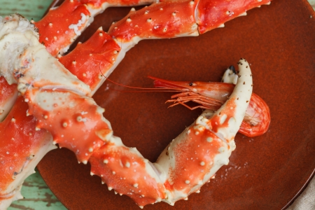 grasping: Crab claw grasping a whole cooked shrimp on a plate accompanoed by additional crab legs to crack open for their meat