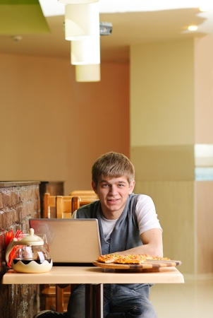 Male Student in pizzeria with Laptop photo