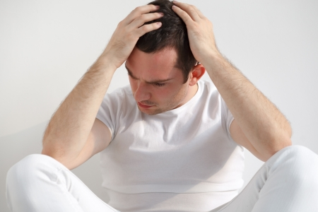 Stressed handsome young man sitting on floor, wearing white t-shirt and pants  Studio shot, natural light Stock Photo - 17283994