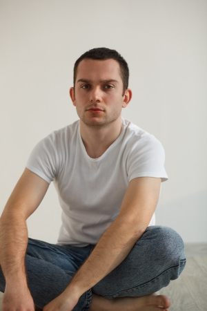 Stressed handsome young man sitting on floor, wearing white t-shirt and pants  Studio shot, natural light Stock Photo - 17283988