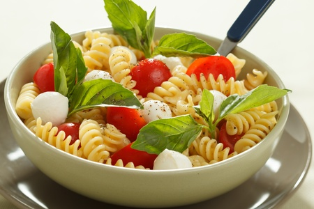 pasta dish: Pasta salad with cherry tomatoes and basil leaves  Stock Photo