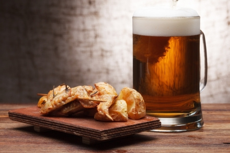 One glass of beer and grilled chicken wings photo