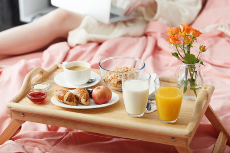 day bed: Breakfast served in bed on wooden tray with coffee and croissants
