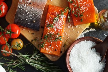 filets: Overhead view of Salmon filets served on wooden cutting board
