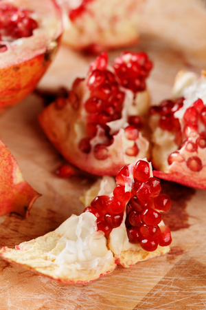ruby red: Fresh peeled pomegranates with ruby red beans on old wooden cutting board, selective focus