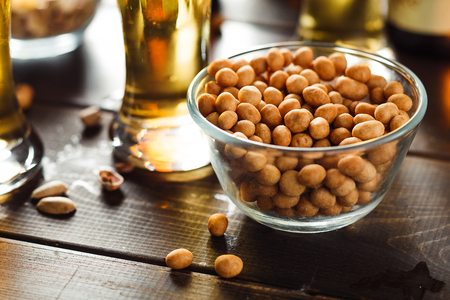 Bowl of nuts and beer on background on wooden table Stock Photo
