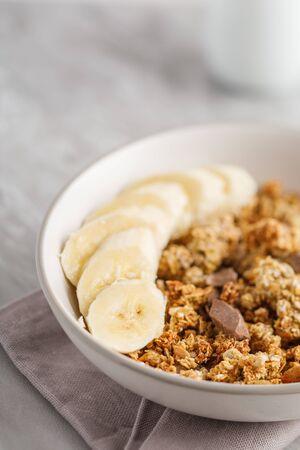 Desayuno con granola con plátano. Trozos de chocolate y tarro de granola en el fondo.