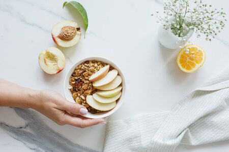 Bowl of granola with nectarine fruit on marble white table. Top view. Female hand holding the bowl