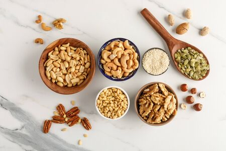 Close-up view of different types of nuts in bowls. Top view