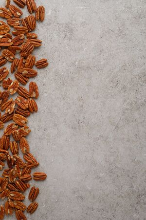 Vertical frame photo of pecan nuts on marble table. Top view, copy space