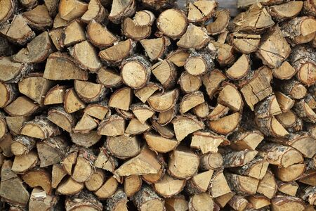 Dry firewood in a pile for furnace kindling firewood texture. Firewood stack. Staple of biomass arranged firewood