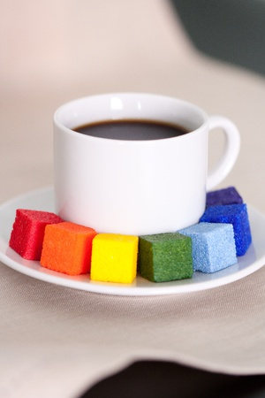Close-up of white cup of coffee with colorful sugar photo