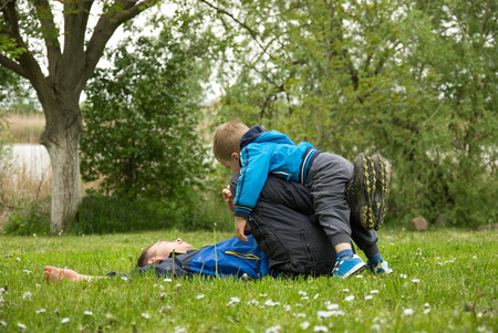 two generations: Dad and son lying in the grass