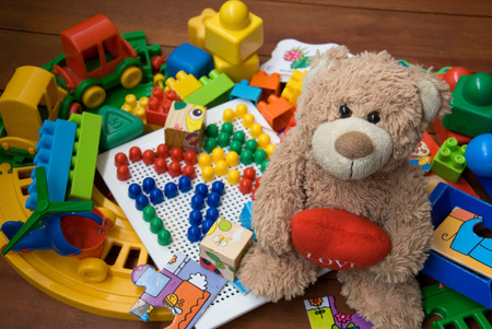 teddy bear surrounded by plastic toys
