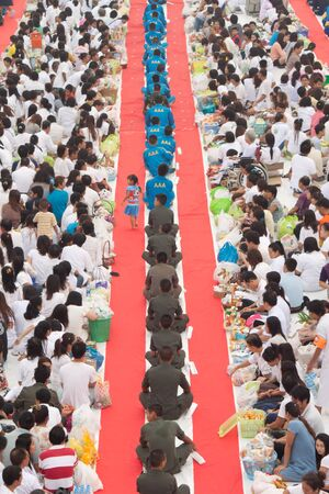 people in rows are waiting for giving alms  Editorial