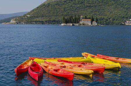 Yellow, orange and red canoes in Adriatic sea, Bay of Kotor, Montenegro.  The shot was taken on sunny day in front of Saint George island. Stock Photo