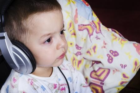 Kleine jongen kijken naar tekenfilms of muziek luisteren voor het slapen gaan. Een jongen die zijn favoriete kussen. Stockfoto