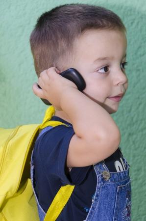 Baby jongen praten op mobiele. Hij draagt een gele rugzak en is klaar om te gaan naar de kleuterschool.