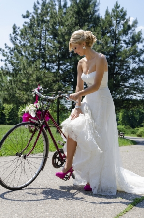 Charming image of a bride with a bicycle wearing purple shoes. The shot was made on a sunny day in the park.