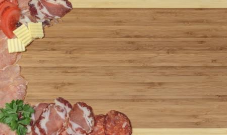 Close-up van houten keuken bord met gehakte gedroogd vlees, peterselie, tomaten en kaas Stockfoto
