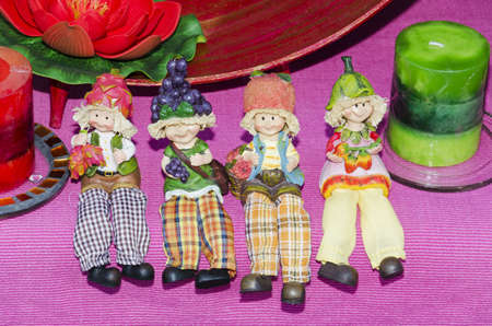 Carnival little dolls with fruit sitting on purple fabric
