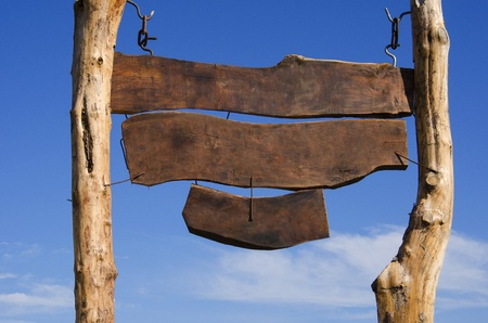 Grote lege houten teken. Drie houten planken werden opgehangen aan twee lange houten pilaren. Stockfoto