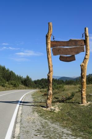 De enorme lege houten teken van de snelweg. Heldere hemel en zonnige dag op de heuvels.