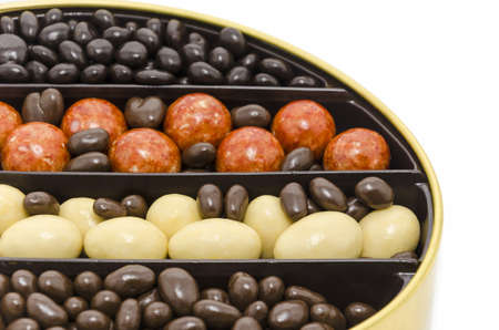 Red, yellow and chocolate candies in a gold box