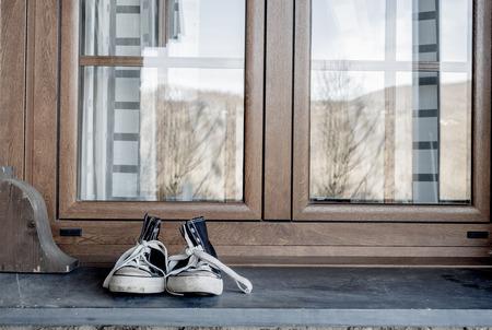 children s feet: Sneakers on window sill