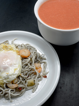 ajillo: Baby eels or elver substitute in garlic sauce a traditional Spanish tapas. Gulas al ajillo with prawns and fried egg and tomato gazpacho soup Stock Photo