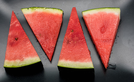 morsel: Four slices of watermelon against black background