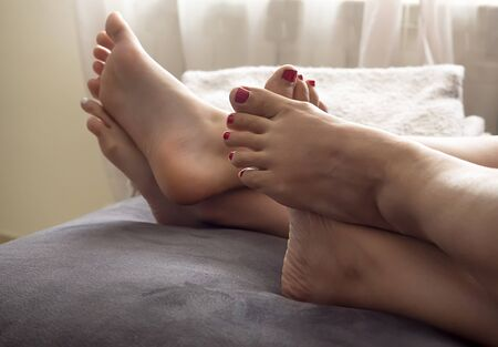 mum and daughter: Mother and daughter on the bed at home with their feet showing Stock Photo