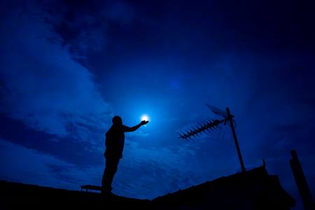 man in the moon: Man up on the roof,  holding full moon in hand against night sky