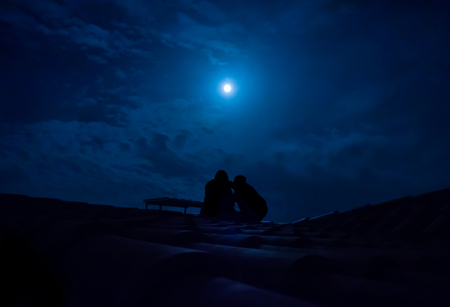 adoration: silhouette of couple sitting on a roof under a full moon Stock Photo