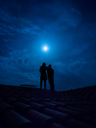 adoration: silhouette of couple on a roof under a full moon