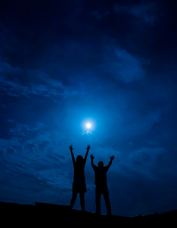 full moon romantic night: Silhouette of couple against full moon with hands up