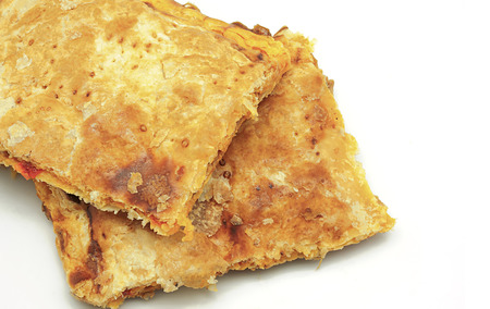 Crispy Empanada Gallega, traditional pie typical from Galicia on a white background