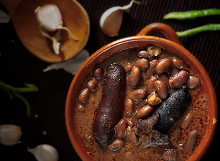 Spanish fabada with Black pudding and sausage in an earthenware dish on rustic background