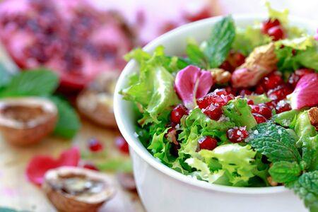 endivia: Ensalada de escarola con granada, nueces, pétalos de rosa, menta, aceite de oliva, vinagre balsámico y sal rosa Foto de archivo