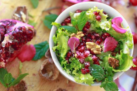 escarola: Vista superior de la ensalada de escarola con granada, nueces, pétalos de rosa, menta, aceite de oliva, vinagre balsámico y sal rosa
