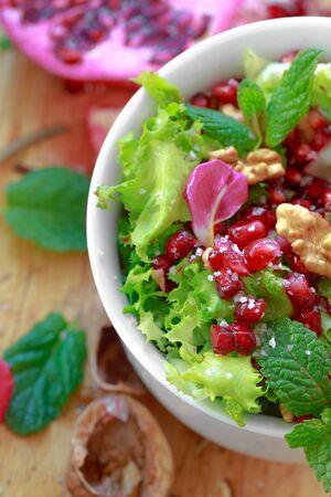 escarola: Ensalada de escarola con granada, nueces, pétalos de rosa, menta, aceite de oliva, vinagre balsámico y sal rosa Foto de archivo