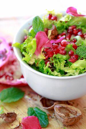 escarola: Ensalada de escarola con granada, nueces, p�talos de rosa, menta, aceite de oliva, vinagre bals�mico y sal rosa Foto de archivo