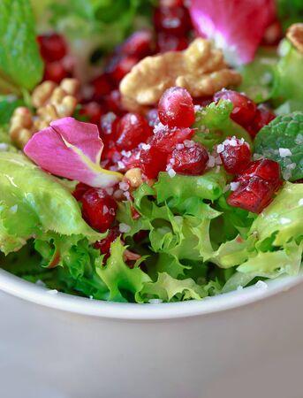 escarola: Cerca de ensalada de escarola con granada, nueces, pétalos de rosa, menta, aceite de oliva, vinagre balsámico y sal rosa