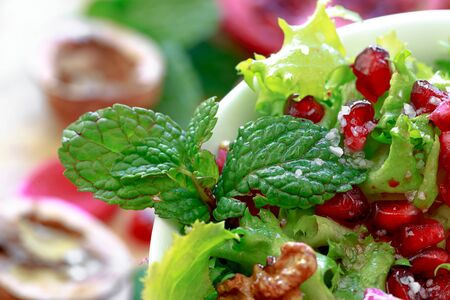escarole: Close up of curly endive salad with pomegranate, nuts, rose petals, peppermint, olive oil, balsamic vinegar and salt