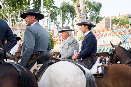courteous: Seville, Spain - April 23, 2015: Horse riders taking a walk by the fair of Seville. The Seville Fair Feria de abril de Sevilla is one of most important celebration of the city, it begins one or two week after easter Holy Week