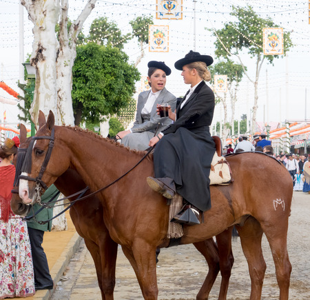 courteous: Seville, Spain - April 23, 2015: Two amazons wearing traditional Andalusian uniforms at the Aprils Fair of Seville. The Seville Fair Feria de abril de Sevilla is one of most important celebration of the city, it begins one or two week after easter Holy Editorial