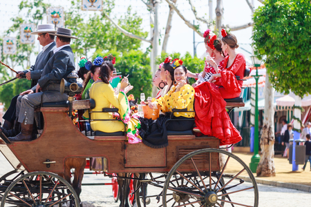 horse drawn carriage: Seville, Spain - April 28, 2015: Young and beautiful women on a horse drawn carriage during the the April Fair of Seville. The Seville Fair Feria de abril de Sevilla is one of most important celebration of the city, it begins one or two week after easte
