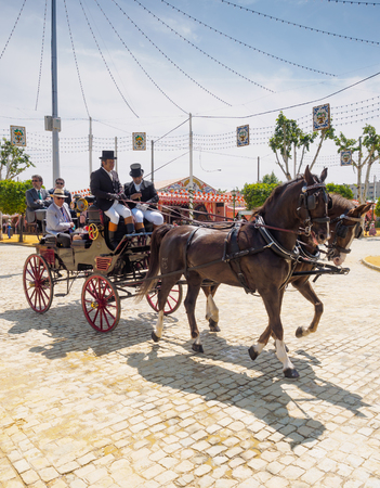 horse drawn carriage: Seville, Spain - April 23, 2015: People travelling in a horse drawn carriage at the Seville Fair. The Seville Fair Feria de abril de Sevilla is one of most important celebration of the city, it begins one or two week after easter Holy Week